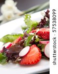 Closeup of plate of spring mix salad with radish, strawberry and chives. White daffodils in background - stock photo