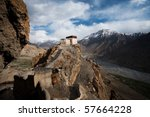 A precariously positioned building overlooks the Himalayan valley below. - stock photo