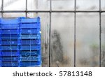 Blue container in front of a greenhouse - stock photo
