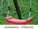 Closeuop of red childrens swing in green grass - stock photo