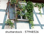 Idyllic half-timbered wall with window partly covered by flowers - stock photo