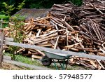 Piles of wood sticks and wheelbarrow behind wooden fence - stock photo