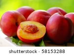 Mature peachs on green background. - stock photo