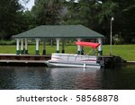 Boat with a red roof at the covered dock - stock photo