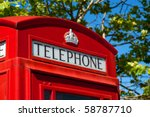 traditional british red telephone call box with a leafy background - stock photo
