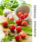 Cherry tomatoes on table and in a bowl with basil and garlic - stock photo