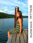 Young Woman Sitting On A Pier In Borneo, Malaysia! - stock photo