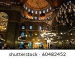 Moslems performing their prayer in the gorgeous Yeni Camii mosque in Istanbul, Turkey - stock photo