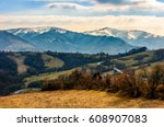 high mountain ridge with snowy peaks. hillside with forest in springtime. road winds through rural fields. Beautiful Carpathian nature. High altitude spectacular view. - stock photo