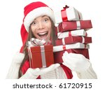 Christmas shopping woman holding gifts wearing red Santa hat. Funny santa woman portrait of a cute, beautiful smiling Asian / Caucasian model. Isolated on white background. - stock photo