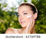 Beautiful sexy woman with fresh health skin applying cream on cheek. Adult girl on nature - stock photo