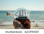 a ship in a bottle held in a persons hand with the beautiful blue pacific ocean as a background - stock photo