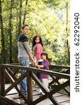 Beautiful scene of young happy family walking in nature together: mother, father and son - stock photo