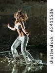 Young woman dancing on street with water. - stock photo
