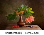 Still Life Autumn concept image with chestnuts and maple leafs - stock photo