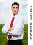 portrait of assured serious businessman against green field and sky - stock photo