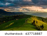 Spring time rural landscape. Wooden fence along the path through agricultural fields in Carpathian mountains - stock photo