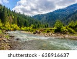 River flows among of a green forest at the foot of the mountain. Picturesque nature of rural area in Carpathians. Serene springtime day under blue sky with some clouds - stock photo