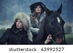 Two sensual female beauties posing with a horse - stock photo