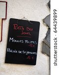 Sign with French text: dish of the day ,moules frites 12 euro and poulee de St. Jacques 14 euro - stock photo