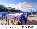 table and chairs at a sidewalk restaurant at a harbor in croatia - stock photo