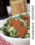 Dutch stamppot, mashed potatoes with kale, topped with vegetarian sausage. Vertical orientation. - stock photo