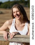 A young caucasian woman laughing in a field - stock photo