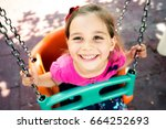 Little Girl Swinging At Playground Outdoors In Summer - stock photo