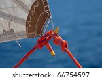 red rope, knot and piece of sail isolated on blue on sailing boat - stock photo