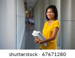 Half portrait of an adorable happy college student holding textbooks and smiling wearing yellow shirt.  Young female Asian Thai model late teens, early 20s of Chinese descent looking at camera - stock photo