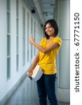 A cute smiling college student in yellow shirt holding books gives thumbs up in a beautifully hallway on a modern university campus. 20s female Asian Thai model of Chinese descent looking at camera - stock photo