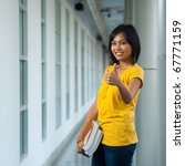 Cute happy high school student wearing yellow shirt holding books smiling while giving a thumbs up on a modern outdoor campus hallway. Teen female Asian Thai model of Chinese descent looking at camera - stock photo