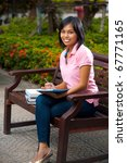 A happy and attractive college student in pink shirt sitting outside on bench smiling looking at camera and writing into her notepad.  20s female Asian Thai model of Chinese descent - stock photo