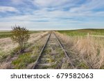 Empty Overgrown Railroad Tracks in Canadian Prairie - stock photo