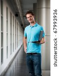 A happy college guy in blue collared shirt arm akimbo holding a laptop standing in a beautiful university campus corridor.  Tall handsome British male caucasian looking at camera head cocked - stock photo
