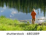 Fishing in lake with reflection of trees and sky - stock photo