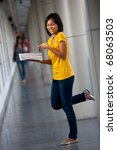 Unhappy young college student in yellow shirt holding, pointing at her textbooks with a disgusted expression balancing on one leg. Twenties female Asian Thai model of Chinese descent looking away - stock photo