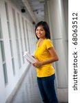 A cute Asian college student wearing yellow shirt, standing sideways, holding textbooks and smiling in a hallway. Twenties female Asian Thai model of Chinese descent looking at camera - stock photo