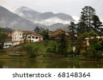 Comfortable houses in mountainous and foggy scenery - stock photo