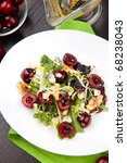 Green salad with cherries, walnuts and blue cheese. Fresh cherries around. Saucer with vinaigrette. - stock photo