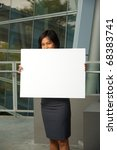 A cute Asian business professional in gray skirt hides face behind a blank sign outside in front of a modern office building.   Custom text copy insert. 20s female Asian Thai model of Chinese descent - stock photo