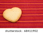 heart shaped cookie on red striped tablecloth - stock photo
