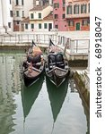 Two gondola in Venice at the pier and buildings - stock photo