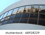 Reflection of apartment buildings and water on huge convex glass window panel - stock photo