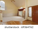 Empty living room with large window with red curtains and white molding - stock photo