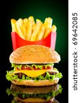 Tasty hamburger and french fries on a green background - stock photo