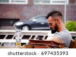 BRATISLAVA, SLOVAKIA - August 12, 2017: A young hipster man with beard and glasses, drinking beer on wooden table outside - stock photo