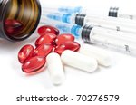 Pills with syringes isolated on white - stock photo