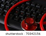 A stethoscope on a keyboard with arranged letters that spell out the word help. - stock photo