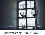 Beautiful crystal glasses for cocktail in front of a window - stock photo